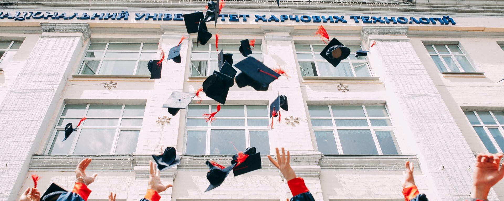 Graduates throwing caps in air